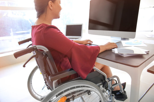 Asian woman in wheelchair working with computer in office
