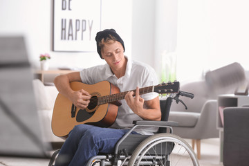 Young musician in wheelchair playing guitar at home