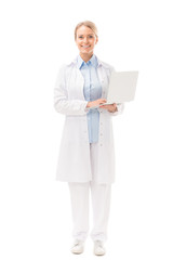 smiling  young female doctor with laptop looking at camera isolated on white
