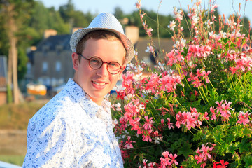 Beautiful sunshine summer portrait of a handsome young hipster man with a hat and glasses with geranium flowers in Brittany, France