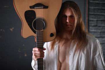 Young man with long hair with a guitar