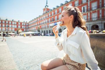 smiling woman at Plaza Mayor in Madrid, Spain eating Empanada