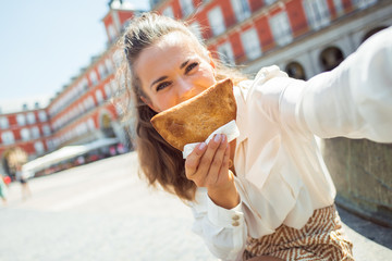 tourist woman taking selfie while making smile with Empanada