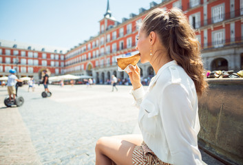 young woman at Plaza Mayor in Madrid, Spain eating Empanada