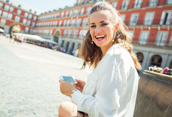 smiling woman at Plaza Mayor in Madrid, Spain writing sms