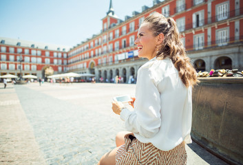smiling young woman at Plaza Mayor in Madrid, Spain writing sms