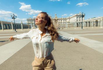 modern woman near Royal Palace in Madrid, Spain rejoicing