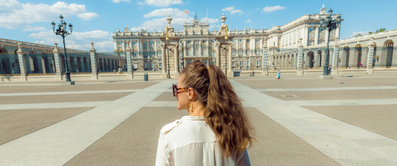 elegant woman in front of Royal Palace looking into distance