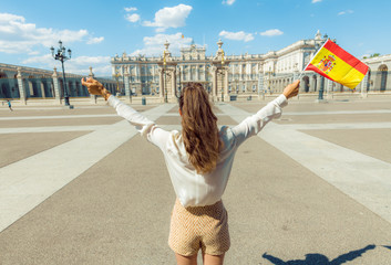 trendy woman with Spain flag rejoicing against Royal Palace