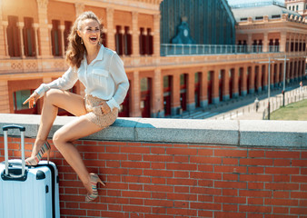 smiling woman looking into distance while sitting on parapet