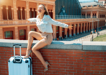 happy young traveller woman rejoicing while sitting on parapet