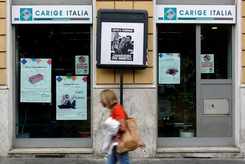 A woman walks past a Carige bank in Rome