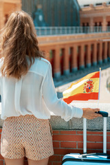 traveller woman with trolley bag, Spain flag and green smoothie