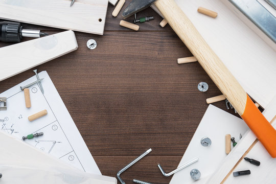 furniture piece parts and tools on the wooden table with copy space during assembly process