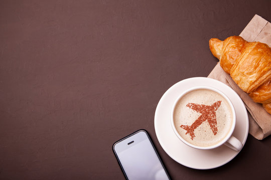 Mug of coffee with an airplane on the foam. Morning coffee with croissant in flight. Smrtrfonom and cup of coffee