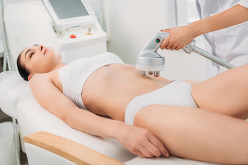 attractive woman getting electrical massage on stomach made by cosmetologist in spa salon