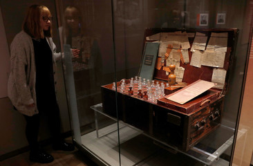 A member of staff poses for a photograph by one of Tsar Nicholas II's travel pharmacy chests at the exhibition, The Last Tsar: Blood and Revolution, at the Science Museum in London
