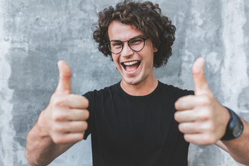 Horizontal shot of handsome happy smiling male with curly hair, wears sepctacles posing for social advertisement with thumbs up on gray concrete wall with copy space for your text.