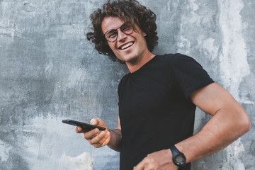 Handsome happy smiling man standing outdoors texting on mobile phone. Young male with curly hair wears spectacles resting outside in the city browsing on his cell phone on concrete gray background.