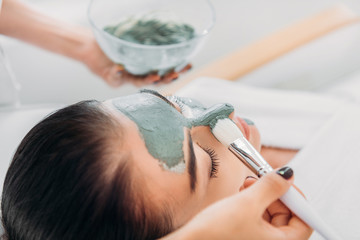 partial view of cosmetologist applying clay mask with brush on female face in spa salon