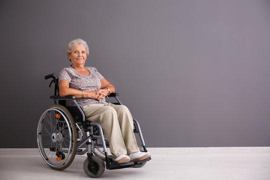 Senior woman in wheelchair near grey wall