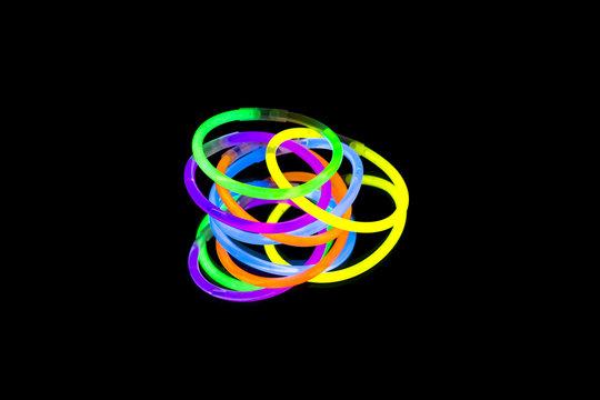 Colorful fluorescent light neon glow stick bracelet strap wristband on mirror reflection black background