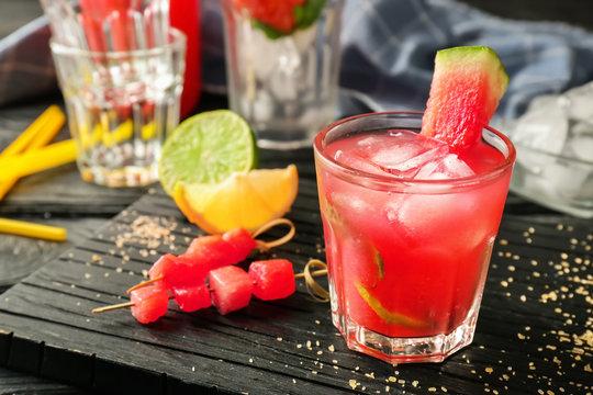 Glass of fresh watermelon lemonade on wooden board