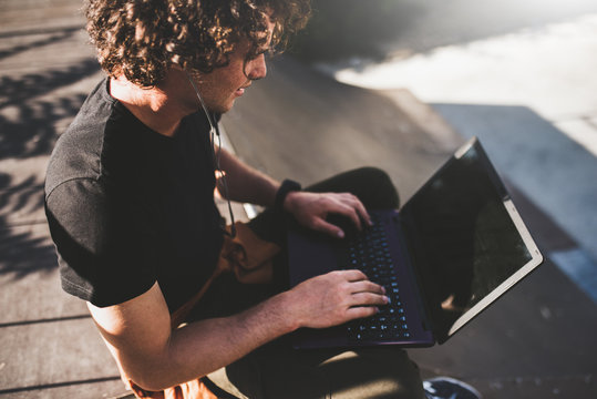 Rear view portrait of male with curly hair using laptop for chatting online with friends and earphones to listening the music, connected to free wireless. Handsome man texting messages to clients