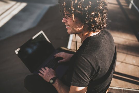 Rear view shot of male with curly hair using laptop for chatting online with friends and earphones to listening the music, connected to free wireless. Handsome man texting messages.