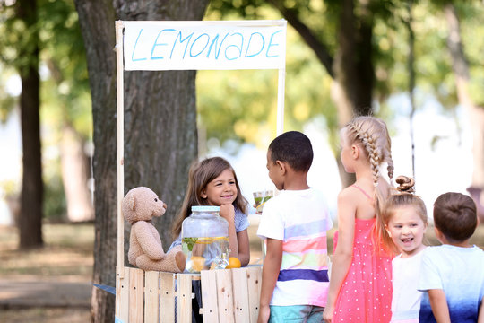 Adorable children waiting in queue for natural lemonade near stand in park