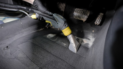 washerman is hoovering automobile carpet, cleaning by foam interior of car in a garage, wearing gloves