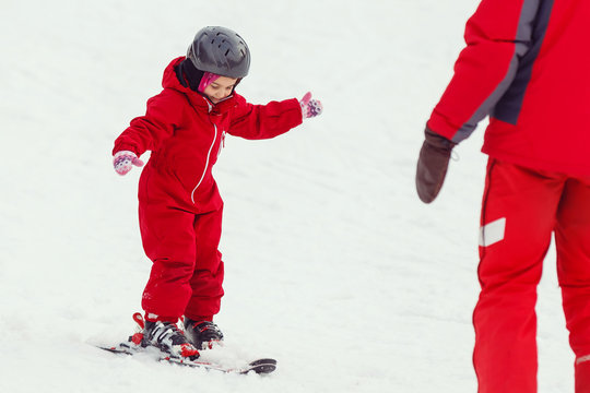 Girl child is learning to ski get up after a fall she slowly slides on skis in soft fresh snow