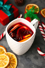 Cup of delicious mulled wine on grey table