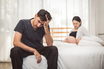 Worried stress man sitting on bed with hand on forehead in bedroom in serious mood emotion with pregnant wife woman background. Major Depressive Disorder called MDD concept. Physical healthcare