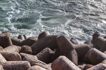 Stones are concrete constructions of the quay of breakers of breakwaters. Close.