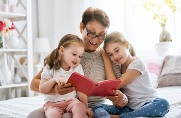 Grandmother reading a book to granddaughters