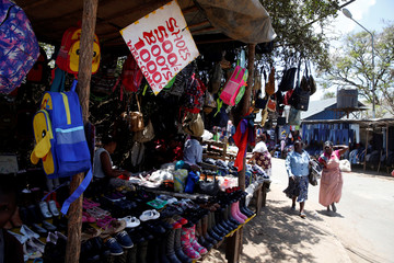Women walk past stores selling shoes and bags at a market in Nairobi, Kenya