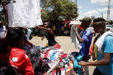 A woman looks at clothing for sale at a market in Nairobi, Kenya