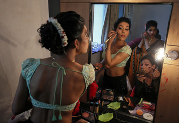 Transgender women apply make-up as they get ready backstage to perform during an event to raise funds for their community in Mumbai