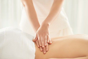 Anonymous massage therapist pressing loin of female client while working in nice massage salon