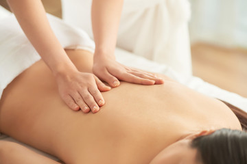 Crop hands of therapist massaging back of unrecognizable female client in spa salon