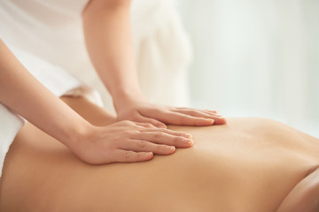 Crop woman massaging back of female client while working in spa salon