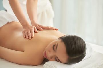 Unrecognizable massage therapist rubbing back of beautiful lady while working in spa salon