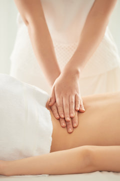 Unrecognizable woman putting pressure on loin of female client during massage session in spa salon
