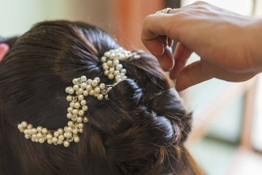 hairdresser takes a bride's hairstyle on her wedding day.black hair of the bride and white decoration on her head.