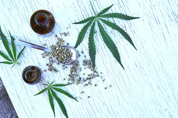 hemp leaves on wooden background, seeds, cannabis oil extracts in jars