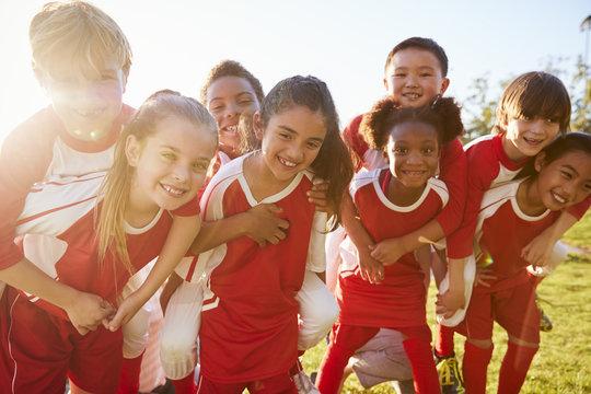 Kids in elementary school sports team piggybacking outdoors