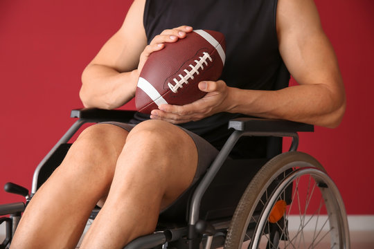 Young man with rugby ball sitting in wheelchair against color wall