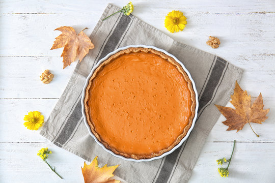 Baking dish with tasty pumpkin pie on white wooden table, top view