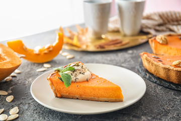 Plate with piece of tasty pumpkin pie on table